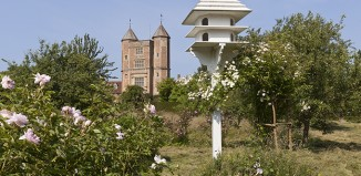 Dovecote in the Orchard at Sissinghurst Castle, Kent, with the Elizabethan Tower seen in the background.