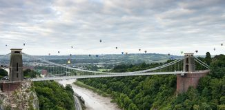 Hot air balloons rising and floating in the air against a cloudy sky, above the city of Bristol and the Clifton Suspension Bridge during the Bristol Balloon Fiesta. River Avon. Credit: Visit Britain