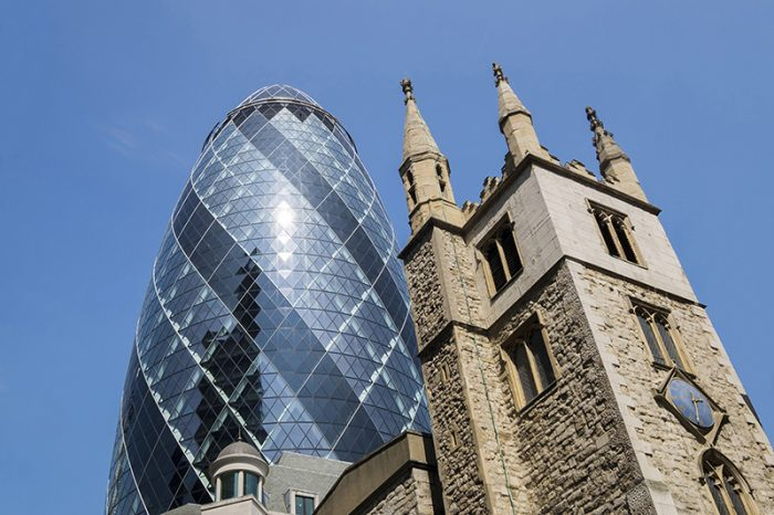 The Swiss Re building known as The Gherkin towering above St Andrew Undershaft in the City of London.