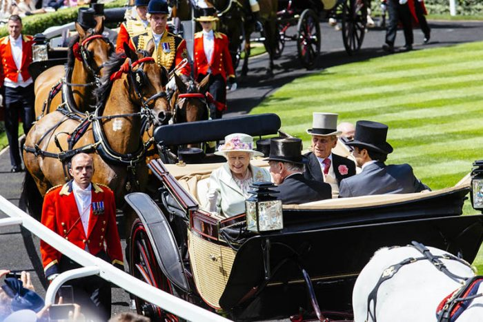 Royal Ascot Race Meeting at the prestigious Ascot racecourse in Berkshire. Royal Procession. Arrival of members of the Royal Family. Queen Elizabeth II and Prince Philip sitting in a horse-drawn carriage with two men. Accompanied by men wearing military uniform walking and on horse-back. Credit: Visit Britain